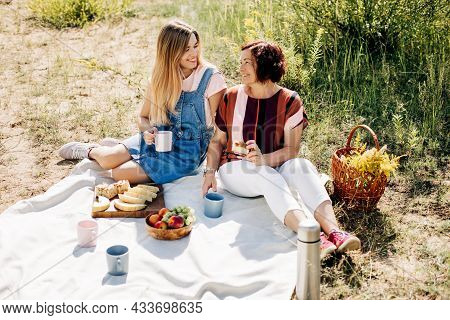 A Smiling Mother And Daughter Are Having A Picnic With Fruits And Pastries On The Lawn. Unity, Time