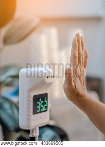 Customer Raised Hand At Digital Thermometer With Temperature Scanning Machine For Fever Before Enter