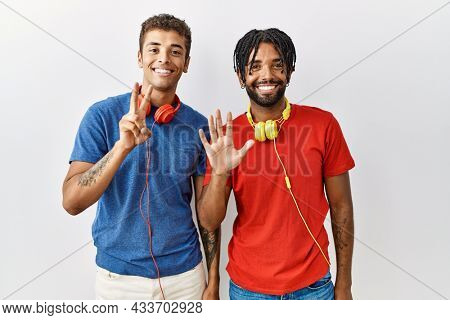 Young hispanic brothers standing over isolated background wearing headphones showing and pointing up with fingers number seven while smiling confident and happy.
