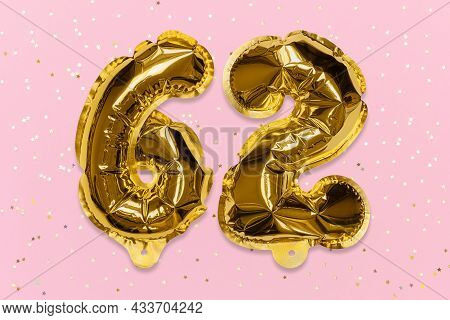 The Number Of The Balloon Made Of Golden Foil, The Number Sixty-two On A Pink Background With Sequin