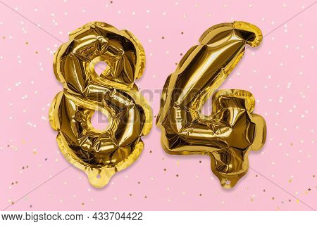 The Number Of The Balloon Made Of Golden Foil, The Number Eighty-four On A Pink Background With Sequ