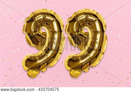 The Number Of The Balloon Made Of Golden Foil, The Number Ninety-nine On A Pink Background With Sequ