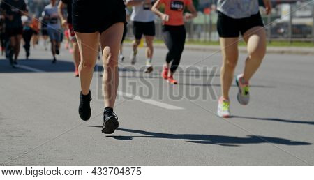 Legs Of People Competing In Marathon In City
