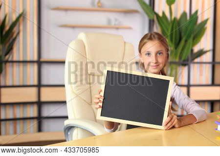 A Young Girl Holds In Her Hand A Drawing Board In A Frame. The Child Holds The Frame In His Hands. A