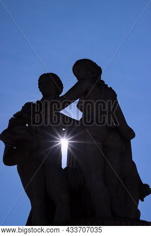 The Silhouette Of Statue Of The Three Graces With Rays Of The Sun. Statue Is Located In Front Of The