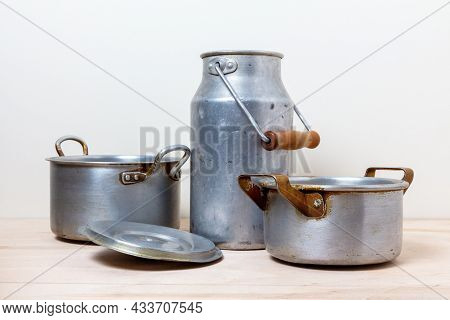 Old Aluminum Pots And A Can On The Kitchen Shelf. Vintage Tableware In Still Life.