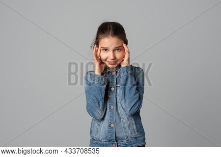 Oops, I Think I Made A Terrible Mistake. Confused Young Girl Clutching Her Head In Panic And Smiling