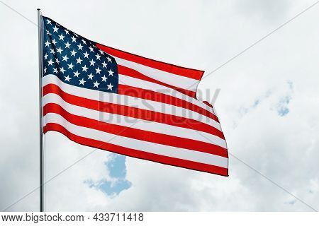 Usa America Flag Waving In The Wind Over Cloudy Sky Low Angle View Close Up.