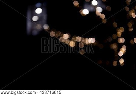 White Abstract Bokeh Made From Buildings And Christmas Lights On Black Isolated Background. Holiday