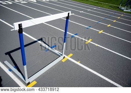 A Lone Hurdle Sits On A Gray Running Track With Fresh Crisp White Lines. No People, Shot In Natural