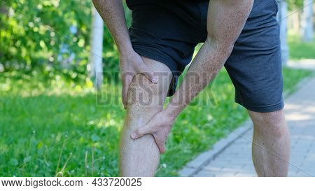Male Athlete Runner Touching Foot In Pain Due To Sprained Ankle. Unrecognizable Athlete Sits On The