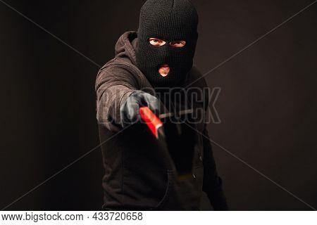 Burglar holding metallic crowbar on black background