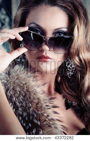 Beautiful glamorous woman posing in fur and sunglasses at studio.
