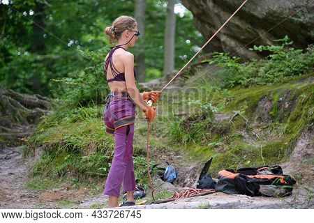 Woman Belays Her Partner Climber With Belaying Device And Rope. Climber's Helper Holding Equipment F