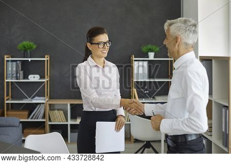 Friendly Male And Female Business Partners Shake Hands To Confirm Their Partnership.