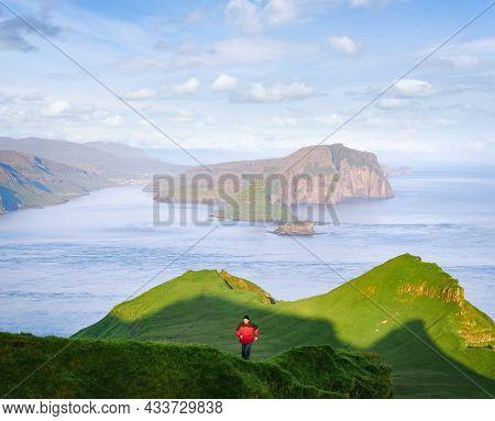 A tourist walks on the island of Mykines overlooking the islands of Tindholmur and Vagar, Faroe Islands