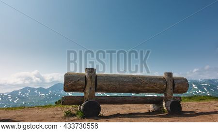 On The Observation Deck There Is A Low Bench Made Of Unpainted Logs. Some Grass On The Ground. Ahead