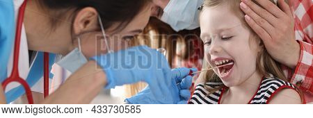 Doctor In Protective Medical Mask Taking Buccal Swab From Little Girl With Cotton Swab