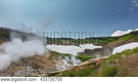 Clouds Of Vapor From Fumaroles Rise Into The Blue Sky. On The Mountain Slopes, Among The Green Veget
