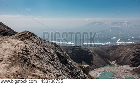 There Is A Turquoise Acid Lake In The Crater Of The Volcano. The Snow Is Melting On The Banks. High