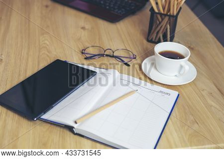Agenda, Planner Book, Calendar, Pencil, Tablet, And Cup Of Coffee Place On Office Desk. Diary For Or