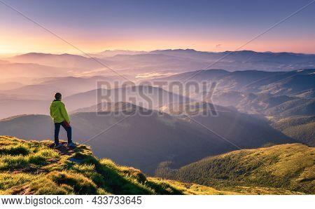 Sporty Man On The Mountain Peak Looking On Mountain Valley