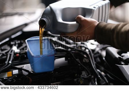 Master Repairman Pouring Motor Oil Into Car Engine Closeup