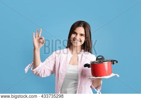 Happy Young Woman With Cooking Pot On Light Blue Background