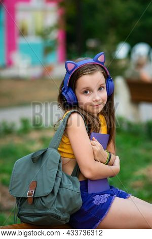 Cute Little Girl In Trendy Outfit Smiling Outside. Preteen School Girl With Book On Bench In Park. P