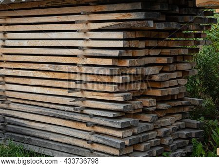 Piles Of Wooden Boards In The Sawmill, Planking. Warehouse For Sawing Boards On A Sawmill Outdoors.