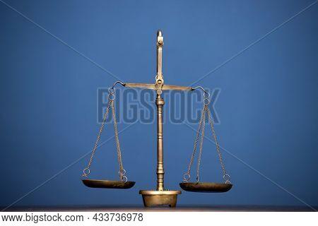 Golden balance scale on blue background