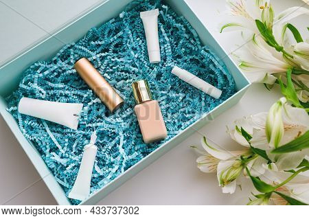 A Package With Decorative And Care Cosmetics And Perfumes In A Blue Box And White Alstroemerias