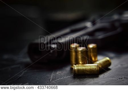 Close-up Of Gunpoint And Bullets On Concrete Table. Pistol For Defense Or Attack. Firearms And Ammun