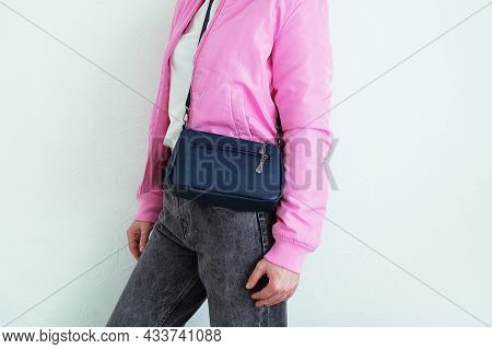Caucasian Woman In Gray Jeans In A White T-shirt In A Pink Jacket With A Blue Bag On Her Shoulder. W
