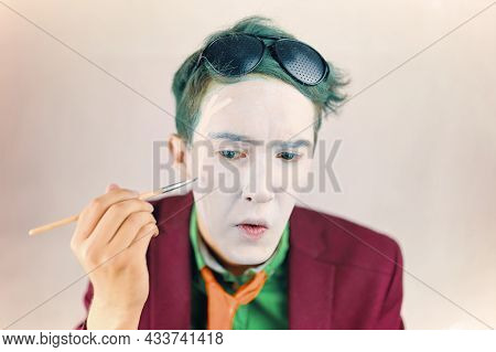 Mim Is Preparing For Performance. Cosplayer Paints His Face With Brush. Actor With White Makeup And