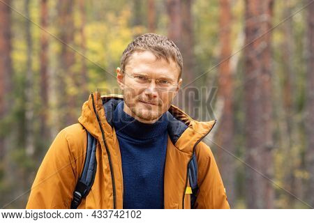 Caucasian Man Wearing Backpack Standing Over Forest Background. A Man With Backpack Walking In The A