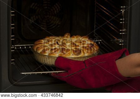 The Finished Cake With Fruit Filling Is Removed From The Oven. A Baker Wearing Heat-resistant Gloves