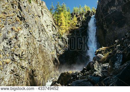 Scenic Autumn Landscape With Vertical Big Waterfall And Yellow Trees At Mountain Top In Sunshine. Po