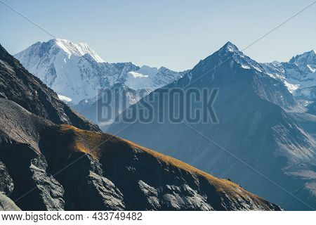 Atmospheric Mountain Landscape With Dark Mountains Silhouettes. Sharp Rocky Pinnacle And Snow-covere
