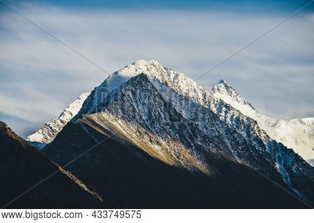 Atmospheric Alpine Landscape With Two Rocky Pointy Mountain Peaks With Snow In Golden Sunshine Under