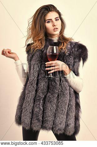 Fashionable Lady Likes Luxury. Fashion Model Long Hair Fur Coat Or Vest Hold Wineglass. Girl Enjoy L