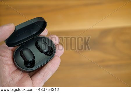 Wireless Earphones With Charge Case In Man Hand Close Up View