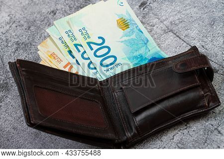 200 And 100 Israeli Shekels Banknotes Stick Out Of A Leather Wallet.