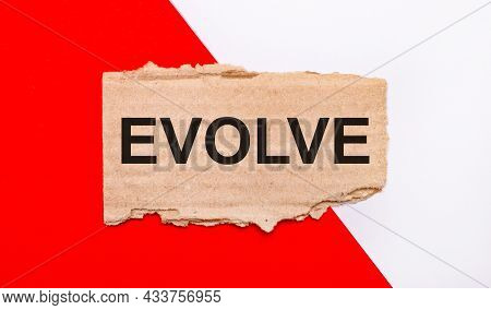 On A White And Red Background, Brown Torn Cardboard With The Text Evolve
