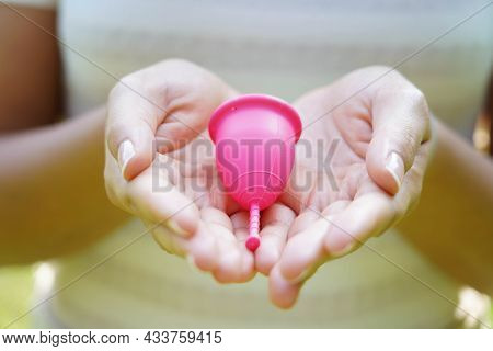 Close-up Of Woman Hands Showing A Pink Collector Menstrual Cup. Alternative Ecological Solution For