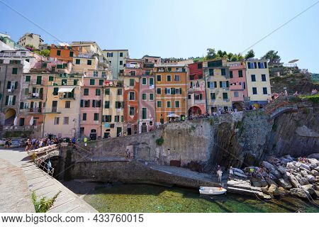 Riomaggiore, Italy - July 20, 2021: Colorful Houses Overhanging Cliffs In The National Park Of Cinqu
