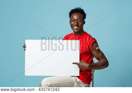 Vaccination Info. Smiling African-american Guy With Plaster On Arm Holding Blank Placard