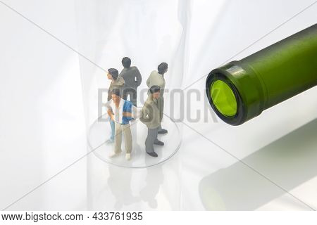 Miniature People. Man Addicted To Alcohol On The Background Of A Bottle Of Wine And A Glass. The Pro