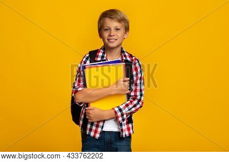 Smiling Calm European Young Boy With Books And Notebooks Ready To Study