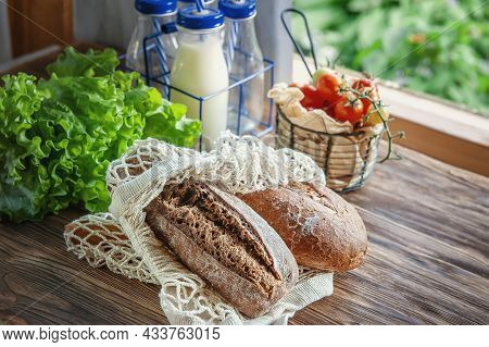 Assortment Of Different Types Of Bread. Fresh Rye Bread And Ciabatta In A Reusable Cotton Mesh For P